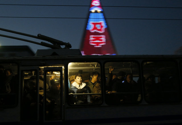 In this December 20, 2018 photo, people ride on a tram as a propaganda message is partially seen displayed on the facade of the pyramid-shaped Ryugyong Hotel in Pyongyang, North Korea. (Photo by Dita Alangkara/AP Photo)