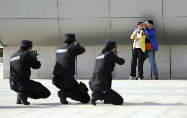Police officers take aim with their weapons at a man playing the role of an attacker as he holds a woman hostage during an anti-terrorism drill at a railway station in Zhengzhou May 10, 2014. An assailant stabbed six people on Tuesday at a railway station in the southern Chinese city of Guangzhou, police and state media said, the latest in a series of attacks that have unnerved the country, some of which Beijing has termed terrorism. (Photo by Reuters/Stringer)