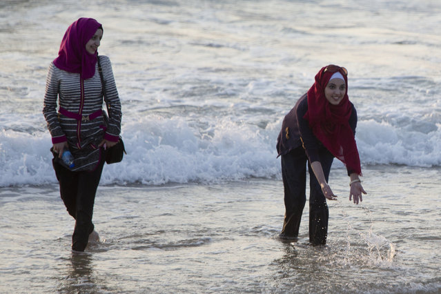 Muslim women bathe in the Mediterranean Sea during the first day of the Eid al-Fitr holiday as the sun sets in Tel Aviv, Israel, Friday, July 17, 2015. The three-day holiday marks the end of the holy fasting month of Ramadan. (Photo by Ariel Schalit/AP Photo)