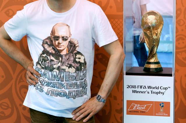 """A man, wearing a T-shirt with an image of Russian President Vladimir Putin, poses for a picture while standing next to the 2018 World Cup trophy during a ceremony to present the trophy to the public in St. Petersburg, Russia, July 18, 2015. Russia will host the 2018 World Cup. The T-shirt reads """"The politest of people"""". (Photo by Peter Kovalev/Reuters)"""