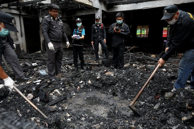 Forensic exports inspect a burnt building at the Pitakkiat Wittaya School in the northern province of Chiang Rai, Thailand, May 23, 2016. At least 18 girls aged from 5 to 12 were killed overnight in Thailand's northern province of Chiang Rai when a powerful blaze swept through a Christian school for girls from poor families. Some of those who survived had to tie cloth together to climb out of the window. (Photo by Athit Perawongmetha/Reuters)