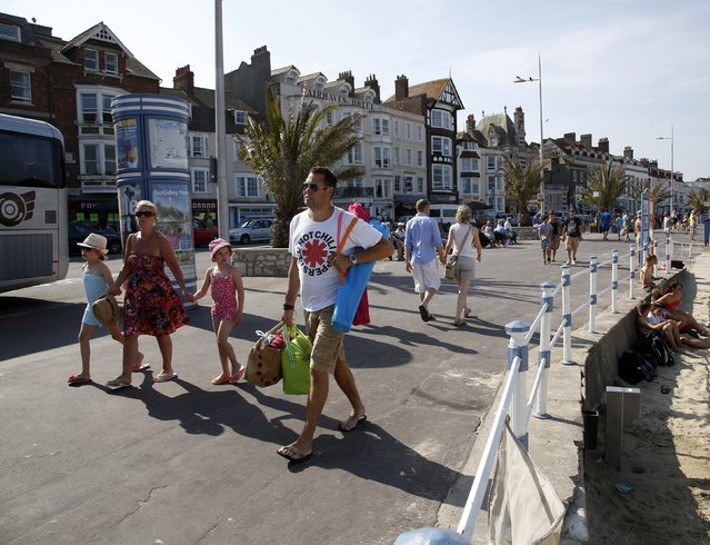 Tourists walk along the beach-front in the Dorset holiday town of Weymouth, England, July 13, 2013. The port was the departure point for thousands of Allied troops who took part in the D-Day landings. REUTERS/Chris Helgren