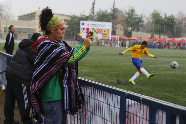 A man uses his mobile phone as a player of Colombia kicks the ball during the Copa Americana of Indigenous People final soccer match against Paraguay at a Stadium in Santiago, Chile, July 25, 2015. (Photo by Ivan Alvarado/Reuters)