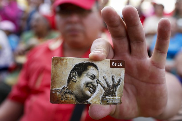 A man holds a prepaid telephone card, with an image depicting Venezuela's late president Hugo Chavez, during a ceremony to commemorate his 61st birthday at the 4F military fort in Caracas July 28, 2015. (Photo by Carlos Garcia Rawlins/Reuters)