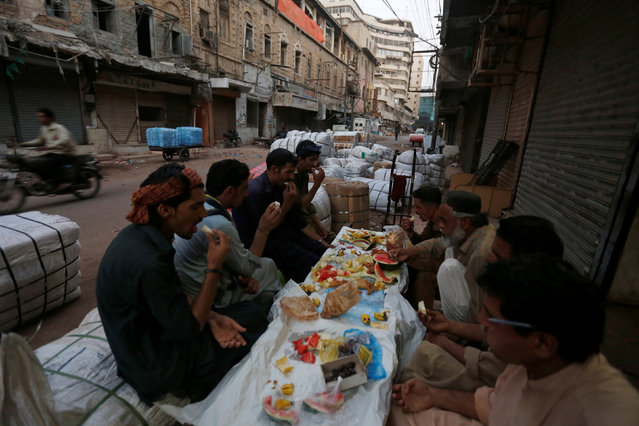 Labourers break fast outside a shop in a market on the first day of the Muslim holy month of Ramadan in Karachi, Pakistan June 7, 2016. (Photo by Akhtar Soomro/Reuters)