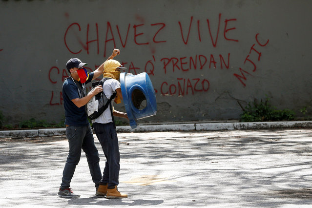 """Demonstrators use a dustbin lid as cover as they clash with riot police officers during a protest called by university students against Venezuela's government in Caracas, Venezuela, June 9, 2016. On the wall reads, """"Chavez live"""". (Photo by Carlos Garcia Rawlins/Reuters)"""
