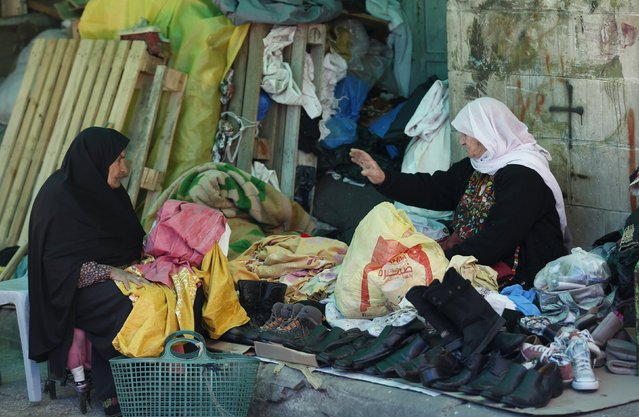 A Palestinian woman sells secondhand clothes and shoes at a market in the West Bank city of Ramallah March 25, 2015. (Photo by Mohamad Torokman/Reuters)
