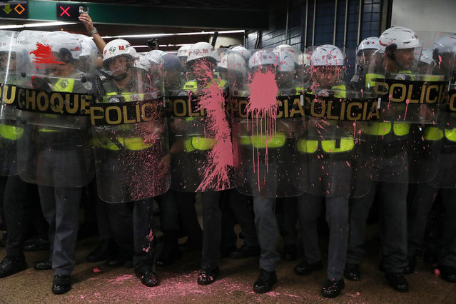 Riot police officers are seen with their shields with paint thrown by demonstrators, who are prevented from jumping over turnstiles, after a protest against fare hikes for city buses in Sao Paulo, Brazil, January 7, 2020. (Photo by Amanda Perobelli/Reuters)