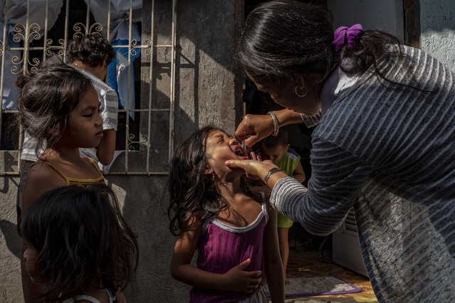 A community health worker administers an oral polio vaccine to a child, during a mass vaccination campaign to combat the resurgence of the polio virus, in a slum area on October 14, 2019 in Manila, Philippines. The Philippines is aiming to vaccinate over 9 million children after the country's health department announced an outbreak of polio, 19 years after the World Health Organization declared the country free of the infectious disease. Health Secretary Francisco Duque has blamed poor immunization coverage and lack of proper sanitation and hygiene as the cause of the resurgence of the disease. The Philippines has been struggling to regain the publics trust in vaccines since 2017, when it was discovered that a dengue vaccine manufactured by French firm Sanofi could cause health risks to people who had not previously had the disease. Recently, the country declared a dengue epidemic after hundreds have died of the mosquito-borne disease. (Photo by Ezra Acayan/Getty Images)