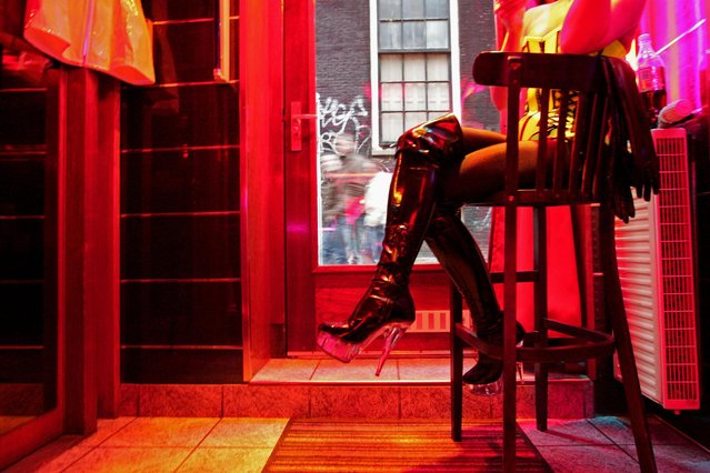 """This file photo taken on December 6, 2008 shows a prostitute, waiting for clients behind her window in the red light district of Amsterdam. From behind their glass walls, at the bends of dark corridors and dark rooms, s*x workers have not waited for the arrival of the world's best science and medicine to become aware of the risk they face by practising the """"oldest profession of the world"""". Emblematic of the Dutch city of Amsterdam, these dens of prostitution come out of the shadows this week while the city hosts the International AIDS Conference from July 23 until July 27, 2018. (Photo by Anoek De Groot/AFP Photo)"""