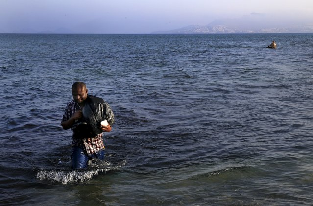 A migrant from Mali walks ashore on the Greek island of Kos after crossing a part of the Aegean Sea between Turkey and Greece, August 8, 2015. The U.N refugee agency, UNHCR, estimates that Greece has received more than 107,000 refugees and migrants this year, more than double its 43,500 intake of 2014. (Photo by Yannis Behrakis/Reuters)