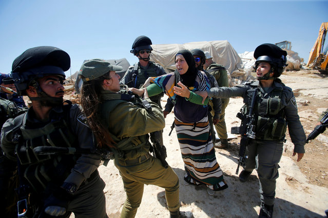 A Palestinian woman scuffles with Israeli troops as they demolish sheds belonging to Palestinians near the West Bank village of Yatta, south of Hebron June 19, 2016. (Photo by Mussa Qawasma/Reuters)