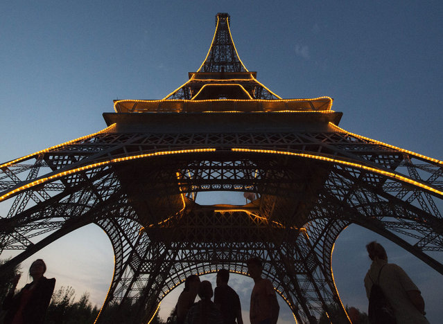 """People walk under an illuminated model of the Eiffel Tower of Paris (12 meters high) in the landscape park Miniwelt (Miniworld) at the event """"Miniworld by Night"""" in Lichtenstein, eastern Germany, Saturday, August 8, 2015. The cultural park Miniworld presents about 100 original and true-to detail buildings and technical facilities at a 1:25 scale ranging on an area of 6.5 hectare. (Photo by Jens Meyer/AP Photo)"""