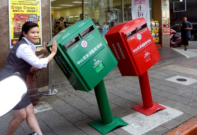 A woman poses next to two mailboxes along a street in Taipei on August 11, 2015 that were reportedly bent by strong winds brought by Typhoon Soudelor over the weekend. The two iron mailboxes have become an unlikely attraction, drawing thousands of snap-happy visitors and have even become a backdrop to a wedding photo shoot. (Photo by Benjamin Yeh/AFP Photo)