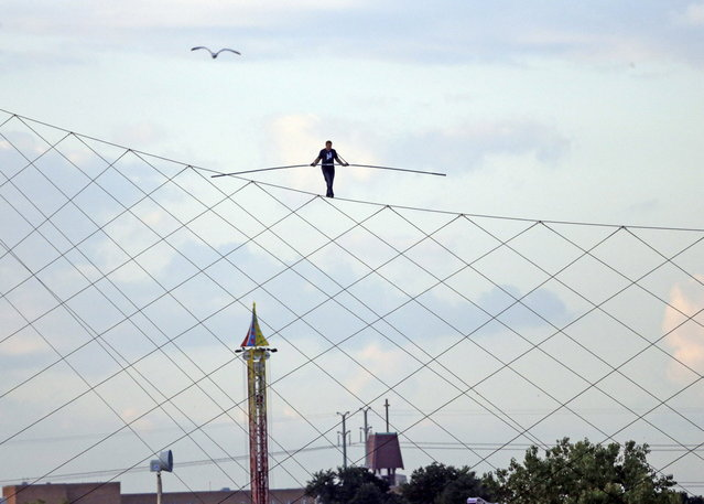 High-wire daredevil Nik Wallenda walks a tightrope above the  Milwaukee Mile Speedway at the Wisconsin State Fair in West Allis, Wis. Tuesday, August 11, 2015. Wallenda completed his longest tightrope walk ever during the appearance at the Wisconsin State Fair. (Photo by Mike De Sisti/Milwaukee Journal-Sentinel via AP Photo)