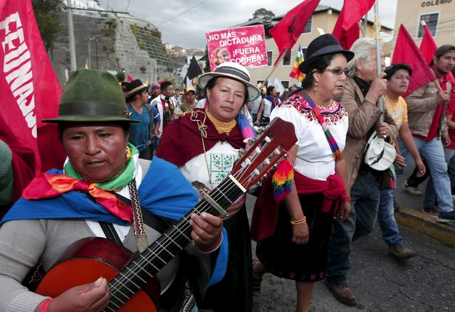 """Protesters march in Quito, Ecuador, August 12, 2015. Ecuadorean Indigenous from the Confederation of Indigenous Nationalities of Ecuador (CONAIE) are arriving in Quito to participate in a nation-wide strike on August 13 against the government of Ecuador's President Rafael Correa, according to local media. The sign in the back reads """"No more dictatorship, Correa out!"""". (Photo by Guillermo Granja/Reuters)"""