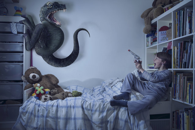 """Christo fights a monster with a """"gun"""" in his bedroom in Laure Fauvel's """"Terreurs"""", 2014, in Paris, France. An imaginative photographer has brought to life monsters that haunt children's nightmares. Armed with sticks, wands and swords the eight and nine year-olds appear to be getting the upper-hand against the villains. Parisian photographer Laure Fauvel, 22, said: I wanted the children not be victims and to fight the monsters. (Photo by Laure Fauvel/Barcroft Media)"""