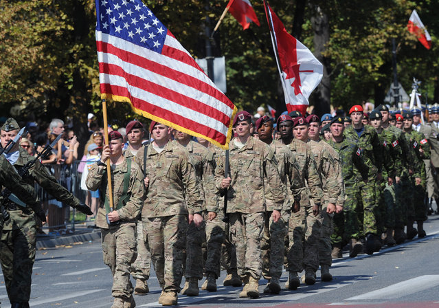 Soldiers from the U.S. and Canada currently training in Poland march during a military parade celebrating the Polish Army Day in Warsaw, Poland, Saturday, August 15, 2015. (Photo by Alik Keplicz/AP Photo)