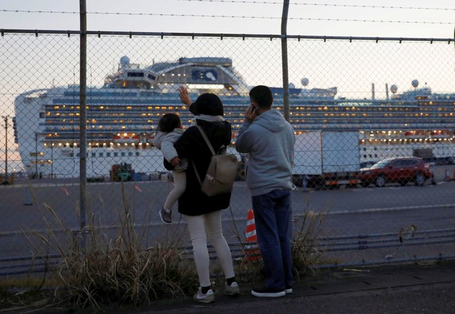Family members of passengers onboard the cruise ship Diamond Princess, where dozens of passengers were tested positive for coronavirus, wave and talk to them on the phone at Daikoku Pier Cruise Terminal in Yokohama, Japan on February 11, 2020. Around 3,700 people are facing at least two weeks locked away on a cruise liner anchored off Japan after health officials confirmed 135 passengers on the ship had tested positive for coronavirus and more cases were possible. (Photo by Issei Kato/Reuters)