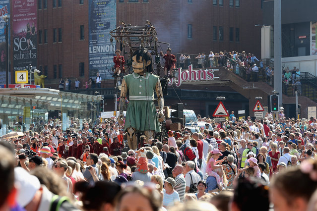Crowds watch as The Little Giant Girl walks through the streets of Liverpool on July 25, 2014 in Liverpool, England. (Photo by Christopher Furlong/Getty Images)