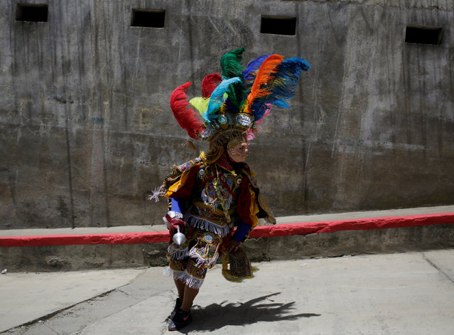 A dancer dressed for the annual procession honoring San Pedro, his town's patron saint, runs through the street of San Pedro Sacatepequez near Guatemala City June 29, 2016. (Photo by Saul Martinez/Reuters)