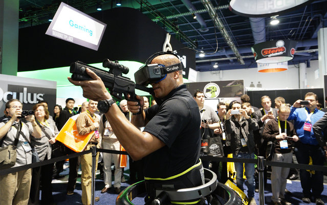A man wearing an Oculus VR headset demonstrates a first person shooter game in a Virtuix Omni virtual reality system at the International Consumer Electronics show (CES) in Las Vegas, Nevada, January 6, 2015. Wearing special shoes with sensors, the player can actually run in the game. (Photo by Rick Wilking/Reuters)