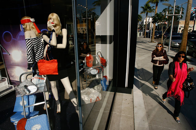 Two women walk past businesses that cater to high-end luxury item consumers along Rodeo Drive on December 14, 2007 in Beverly Hills, California. In the midst of the biggest selling season of the year, retailers for America's richest consumers are losing their least-affluent customers, those who buy luxury items only when they have the cash to spend, while the richest continue buying designer merchandise at a healthy clip. (Photo by David McNew/Getty Images)