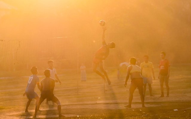 People play volleyball during sunset at a ground in Naypyidaw on January 17, 2020. (Photo by Ye Aung Thu/AFP Photo)