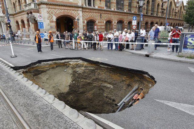 A hole in the road following a storm the day before on Fovam square in Budapest, Hungary, 18 August 2015. (Photo by Zsolt Szigetvary/EPA)