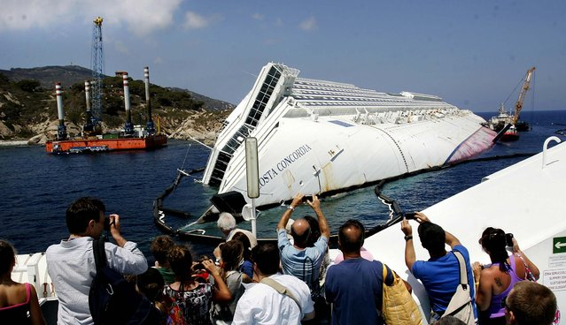 Tourists take photographs of the Costa Concordia wreckage as they arrive on a ferry to Giglio Island, Italy