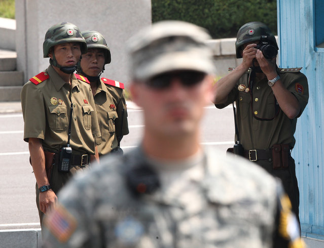 North Korean soldiers watch the south side as a U.S. Army soldier stands guard after a ceremony marking the 61th anniversary of the signing of the armistice agreement that ended the Korean War, at the border villages of Panmunjom, South Korea, Sunday, July 27, 2014. North Korea fired a short-range ballistic missile into waters off its east coast on Saturday, a South Korean defense official said, adding to its unusually high number of weapons tests this year. (Photo by Ahn Young-joon/AP Photo)