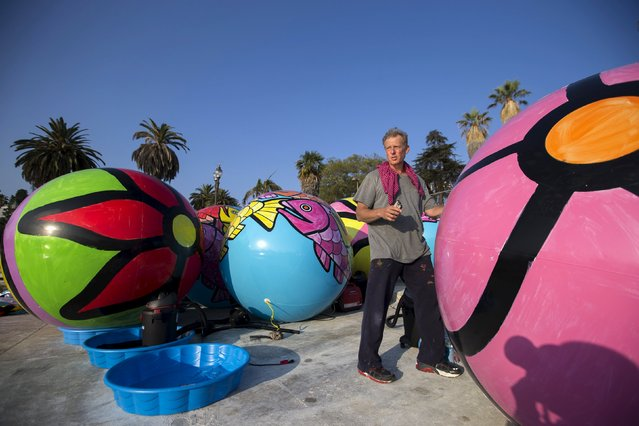 "Portraits of Hope co-founder Ed Massey moves inflated spheres to be lowered in MacArthur Park Lake during the installation of Portraits of Hope's exhibition ""Spheres at MacArthur Park"" in Los Angeles, California August 21, 2015. (Photo by Mario Anzuoni/Reuters)"