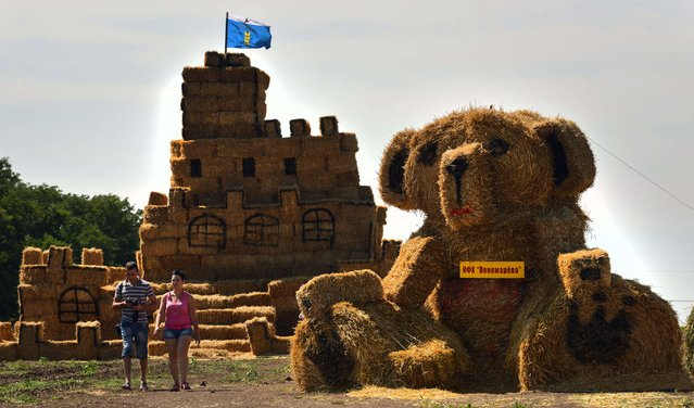 People walk past sculptures made with straw on August 4, 2014 during a contest in the village of Krasnoye, some 38 kilometers outside the southern Russian city of Stavropol. (Photo by Danil Semyonov/AFP Photo)
