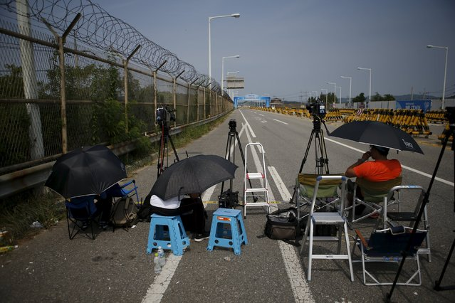 Journalists wait for vehicles transporting South Korean delegation at a checkpoint on the Grand Unification Bridge which leads to the truce village Panmunjom, just south of the demilitarized zone separating the two Koreas, in Paju, South Korea, August 24, 2015. (Photo by Kim Hong-Ji/Reuters)
