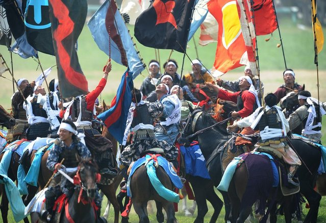 """Local people in samurai armor ride their horses as they try to catch a yellow sacred flag (not pictured) at the annual Soma Nomaoi Festival in Minamisoma, Fukushima Prefecture, on July 29, 2012. Some 400 horses and thousands of people took part in the 1,000-year-old """"Soma Nomaoi"""", or wild horse chase, at the weekend in the shadow of Japan's crippled Fukushima nuclear plant. (Photo by Toru Yamanaka/AFP Photo)"""