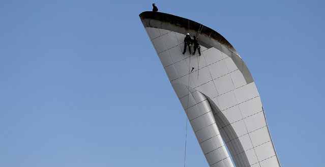 Workers abseil from the top of the Olympic cauldron inside the Olympic park in preparation for the 2014  Winter Olympics in Sochi, February 2, 2014. (Photo by Phil Noble/Reuters)