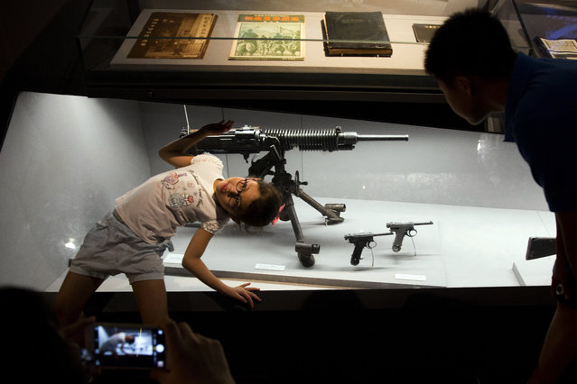 A child poses for photos near confiscated Japanese weapons displayed at the Memorial Museum of Chinese People's War of Resistance against Japanese Aggression in Beijing Saturday, August 29, 2015. (Photo by Ng Han Guan/AP Photo)