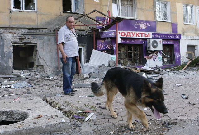 A man with a dog stands in front of a building damaged by, what locals say, was recent shelling by Ukrainian forces, in Donetsk, August 20, 2014. (Photo by Maxim Shemetov/Reuters)