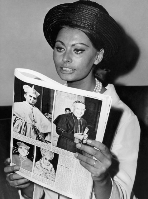 Italian movie star Sophia Loren sits reading a magazine carrying an article about the current Conclave for the election of a successor to the late Pope John XXIII, in Rome, June 21, 1963 at the headquarters of the association of Italian movie producers. Cardinals shown in magazine pictures are, top row only, Giovanni Battista Cardinal Montini, Archbishop of Milan, who later that same day was elected Pope and took the name Paul VI (left). Right is Giacomo Cardinal Lercaro, Archbishop of Bologna, who also was a very strong candidate to Papacy. (Photo by AP Photo)