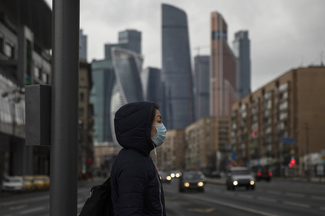 A woman wearing face mask waits to cross a nearly empty road due to residents taking the advice of staying at home to avoid the spread of the coronavirus, with Moscow City skyscrapers in the background, in Moscow, Russia, Thursday, April 2, 2020. Online shopping for food and other supplies has boomed in Moscow after the authorities put most residents on lockdown. (Photo by Pavel Golovkin/AP Photo)