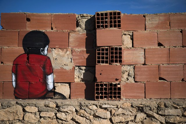 """A mural by Brazilian artist Tinho decorates a wall in the village of Erriadh, on the Tunisian island of Djerba, on August 7, 2014, as part of the artistic project """"Djerbahood"""". (Photo by Joel Saget/AFP Photo)"""