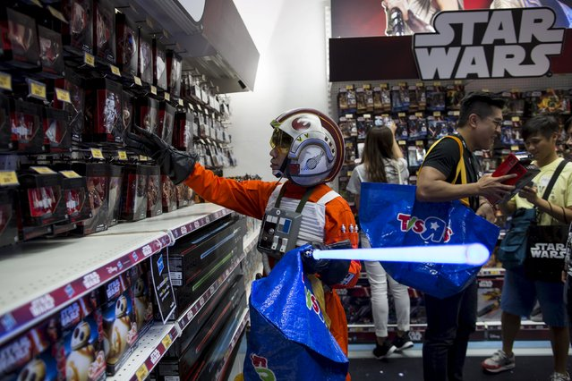 """A fan dressed up as Luke Skywalker picks new toys from the upcoming film """"Star Wars: The Force Awakens"""" on """"Force Friday"""" in Hong Kong, China, September 4, 2015. (Photo by Tyrone Siu/Reuters)"""