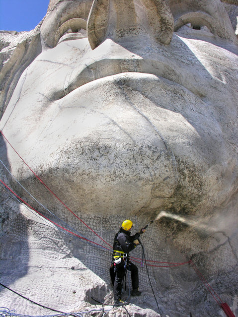 A man cleans a part of Mount Rushmore in South Dakota. (Photo by Caters News Agency)