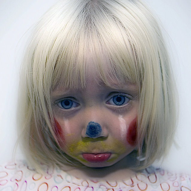 "Sad Clown. ""God I love face painting day at daycare. Today Frankie came home as a clown. Which should be a happy thing but I always think of clowns as sad so I immediately said ""time to take pictures"" and ""make your sad face"". She takes direction so well for an almost three year old. Later, we were in the back yard with the dogs and Colonel Mustard had an apple and jumped on the lawn chair to eat it. Frankie turns to me and says ""We need a picture of this"". That's my girl!"" – Rich. (Photo by Rich)"