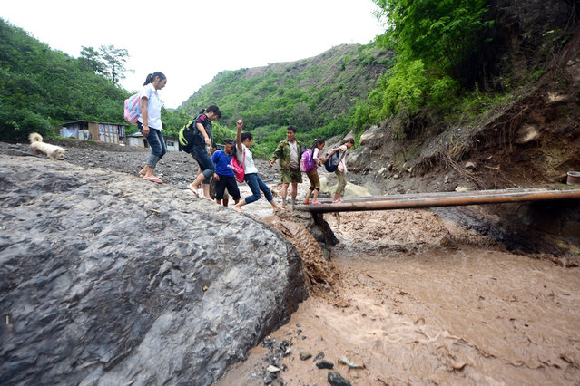 Schoolchildren get a helping hand as they cross a makeshift bridge to get to school after a mudslide that occurred in Ningnan, southwest China's Sichuan province on July 1, 2012. (Photo by AFP Photo)