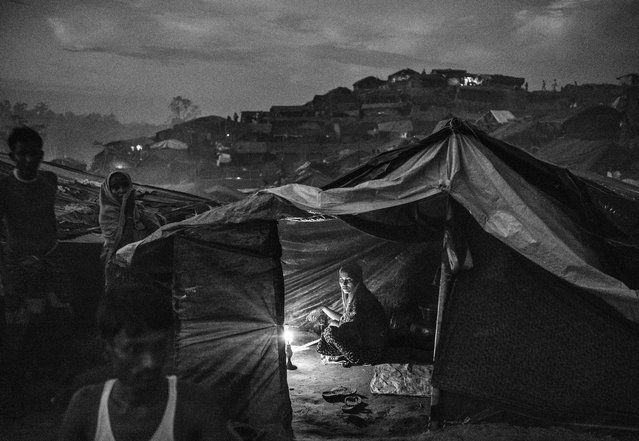 A Rohingya refugee woman uses a candle to light her tent at the Palongkali refugee camp, on October 1, 2017 in Cox's Bazar, Bangladesh. (Photo by Kevin Frayer/Getty Images)