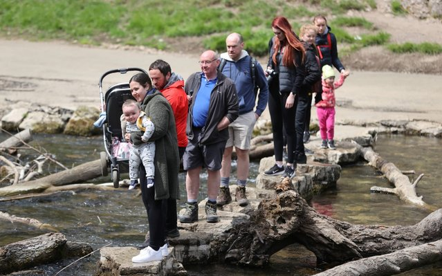 People walk on rocks to cross the River Dove in Dovedale in the Peak District, following the outbreak of the coronavirus disease (COVID-19), Ashbourne, Britain, May 16, 2020. (Photo by Carl Recine/Reuters)