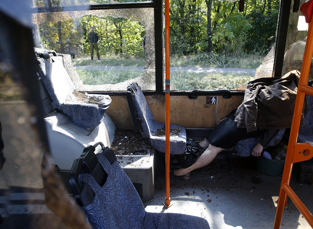 The body of Tatiana Medvedeva, killed in an attack on a bus, is seen covered by a jacket in the town of Donetsk, eastern Ukraine, Tuesday, September 16, 2014. The casualties come as Ukraine's parliament plans to review a bill that would give greater autonomy to the eastern regions of Donetsk and Luhansk, where fighting between separatists and Kiev's forces has claimed at least 3,000 civilian lives. (Photo by Darko Vojinovic/AP Photo)