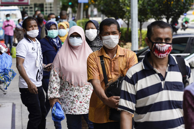 Muslims wearing masks wait outside a wet market in downtown Kuala Lumpur, Malaysia, Friday, April 24, 2020. Malaysia, along with neighboring Singapore and Brunei, has banned popular Ramadan bazaars where food, drinks and clothing are sold in congested open-air markets or road-side stalls. The bazaars are a source of key income for many small traders, some who have shifted their businesses online. (Photo by Vincent Thian/AP Photo)
