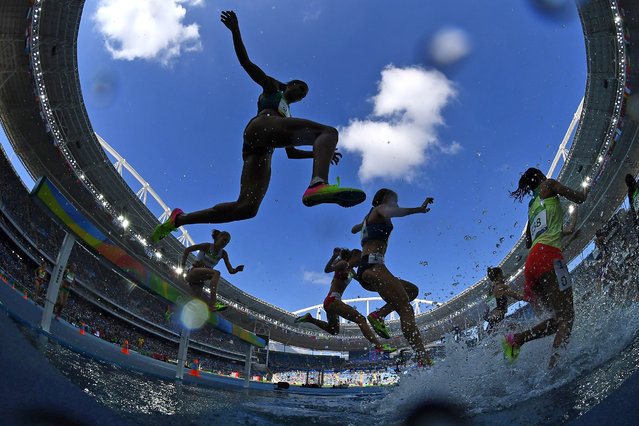 Athletes compete in the Women's 3000m Steeplechase Round 1 during the athletics event at the Rio 2016 Olympic Games at the Olympic Stadium in Rio de Janeiro on August 13, 2016. (Photo by Franck Fife/AFP Photo)